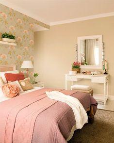 Dormitorio con papel pintado verde con flores, ropa de cama rosa viejo y muchos cojines, tocador con banqueta y espejo con luces de camerino