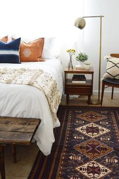Global bohemian bedroom design in neutral color scheme with lots of texture Featuring a rustic wood bench, Moroccan wedding blanket, and antique rug - Modern Global Home Ideas & Decor