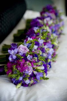 A soft bouquet of purple, blue, raspberry and lavender flowers; Lisianthus, Stock, Anenome and Freesia. The stems tied with Purple double faced satin ribbon. {Design: TableArt | Photo: Susan Beard Design}