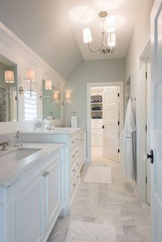 Pretty Master Bathroom with soft blue-gray walls, marble counters, and white wood framed mirrors