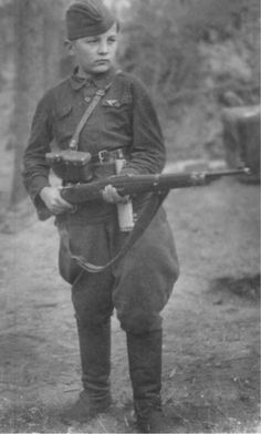 "Thirteen-year-old scout and partisan Fyodor Moshchev. The author's capture to the photo – ""A boy was given a German rifle"". Probably, it's a standard Mauser 98K with a sawed-off butt so that it was easy for the boy to handle it. October 1942."