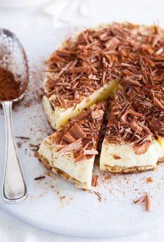 Recept voor tiramisutaart met chocolade krullen -1 biscuitbodem van 1 cm dik of kant-en-klare taartbodem -1 kopje espresso -2-3 el koffielikeur -3 blaadjes witte gelatine -3 eidooiers -100 g suiker -1 bakje mascarpone (250 g) -200 ml slagroom -50 g pure chocolade -cacaopoeder