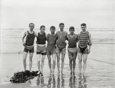 """New Zealand circa 1910. """"Unidentified bathers, probably at Christchurch."""" - by Steffano Francis Webb. (By 1910, men's bathing costumes were sleeveless and cut off at mid-thigh. However, as required by some bylaws, many male bathers, such as this group, wore trunks over their one-piece suits.) Click to view full size - large."""