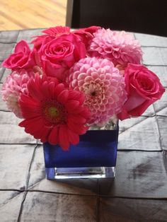 dahlia, gerber daisy, roses, clear vase wrapped in blue crepe paper