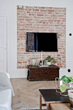 ściana z czerwonej cegły w salonie,drewniana skrzynia kufer retro w roli komody TV