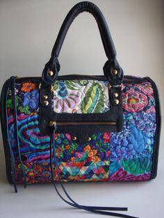 Bolsa feita de tecido de algodão quiltada e com laterais e alças de couro ecológico. Possui alça de mão e transversal