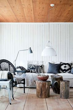 Living spaces inspiration | White painted paneling with wood planked ceiling, black and white textiles, oversized pendant light and tree stumps used as coffee table