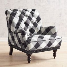 Come home to a comfortable seat, offered here in a timeless buffalo check. Overstuffed and hand-tufted, our Chas Armchair comes with vintage charm to spare: Rolled back and arms, hand-applied nailhead trim, black piping and turned hardwood legs.