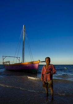 Kid In Front Of A Dhow On The Beach, Vilanculos, Mozambique