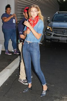 Gigi Hadid wears a cropped denim shirt with jeans, silver oxfords, and a silk scarf