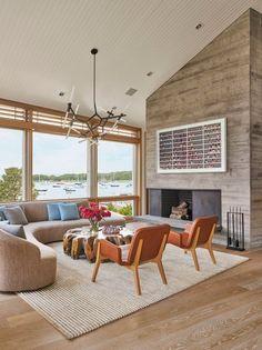 O living integra vários espaços como lounging, jantar, cantinho de leitura e sala de estar. Mudanças de nível no chão ajudam a definir as diferentes áreas e também auxiliam no alinhamento da casa com o terreno irregular.