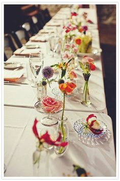 Love this simple single flower arrangements in varying colors and types. Delicately dresses up an all white table.