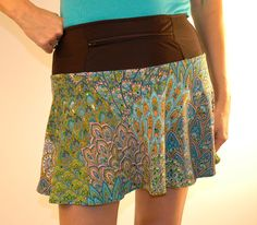 """PeacockLily SwingStyle As sweet as a lily, this lightweight skirt has soft shades of pinks, blues, and greens. Black wicking anti-ride undershorts hold two 5X5"""" pockets and the reverse flat-feld seams help resist chafing! The 12"""" zippered pocket in the waistband can be worn front or back. Don't forget to grab the matching headband! Originally $65, now $60. Non-returnable."""