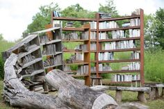 """""""Stacks"""" is an outdoor bookshelf installation by artist David Harper made of books and wood. The theme for Harper's installation: """"these trees shall be my books,"""" comes from William Shakespeare's """"As You Like It,"""" but the goal of the work goes far beyond Orlando's wish to immortalize Rosalind. Harper seeks to immortalize the love of knowledge, and the homage owed to the living things we use to create stores of knowledge for all to study."""