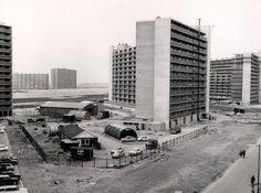 tot: 1970-12-31 Beschrijving: Links een stukje van de Beneluxflat op het Chopinplein, midden de Europaflat op het Griegplein en rechts de Rijnmondflat op het Sibeliusplein in de wijk Groenoord. De flats op de achtergrond staan in de Vlaardingse wijk Holy. Tussen beide wijken ligt het dijklichaam voor de omstreden rijksweg 19.