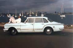 Our daughter on Gertie, a 1962 Plymouth Valiant.  San Diego harbor in the background during a rare storm system.  Shot from Shelter Island.  Film-based photo, early 90's.