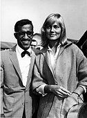 Sammy Davis Jr. greeting May Britt as she arrives in London - Stock Photo