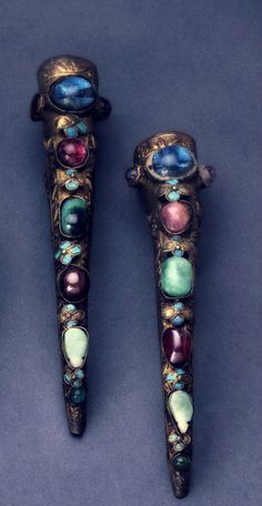 Pair of nail covers in gilt-washed metal mounted with colored glass and jade cabochons. China.