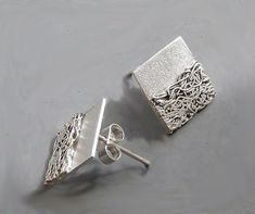 These contemporary square studs are completely hand made in sterling silver and 999 pure silver . They have been textured partially oxidized and