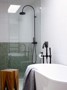 bathroom with white stacked tiles, green terrazzo, black tapware.