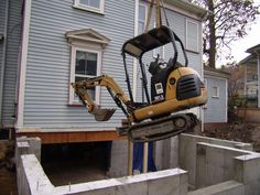 Lowering the mini excavator into the basement