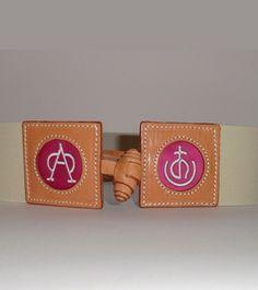 Cinturón elástico hierros deganaderíaconfeccionado enpiel, con detalle de ganadería en fucsia o rojo y cierre de botón. Hecho por la marca Purezaen España. Regulable, de la talla 38 en adelante. Elegante y estiloso paravestir informal yen dos colores: marfil y rosa palo.