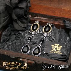 Alchemy Gothic E315 She Walks In Beauty Dropper Earrings (pair)  A pair of black cabochon and etched brass, pewter earrings with black bead and Swarovski crystal droppers; with surgical steel ear-posts.