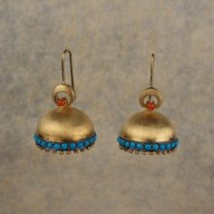 Turquoise and corals team up in this pair of jhumkis handcrafted in sterling…
