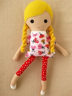 Doll: Beautiful sunshine blond hair in braids White top with different colored ladybug print Red leggings with white dots White flats