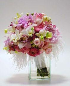 Buquê de Plumas, feito em espiral com orquídeas denphale, orquídeas cymbidium, peônias, rosa spray e ranúnculos, com acabamento de plumas e fita de cetim.