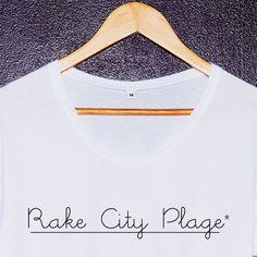 «Rake City Plage*» by St Paul*, dédicace à la ville du vice et des plages !x Disponible en coupe Femme et Hommex 100 % Cotonx Coupe Femme Loose, Col rond large, Manches retroussées