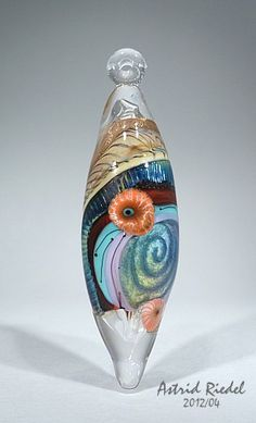 Astrid Reidel glass bead, 80mm long,  it has a 3D spiral, a pleated section of silverglass, twisted raku stringer goldstonestringer, transparent orange and emameled murrini poppies, and on top of it all it is hollow!