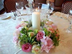 nido de flores y vela grande para decorar la mesa de tu boda