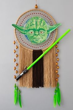 """Dream Catcher """"Master Yoda"""". Unique wall hanging inspired Star Wars character. Detailed oil hand painted on leather canvas Yoda's head with ears and hair, original costume, green removable lightsaber which glows in the dark, place for the personal inscription on the back side and wise smile. This is an incomplete list of the main features of this dream catcher."""