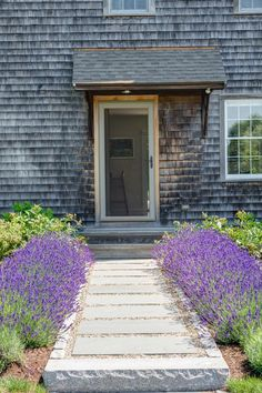 This pastoral garden by Nilsen Landscape Design, LLC, is filled with lavender, daisies, and other attractive plants which create a colorful contrast to the gray weathered cedar siding of the home.