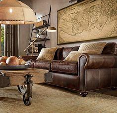 dark brown leather sofa, ecru silk linen and woven suede pillows, railroad cart coffee table, burlap dome pendant, brass task floor lamp, large framed map, honey braided hemp rug