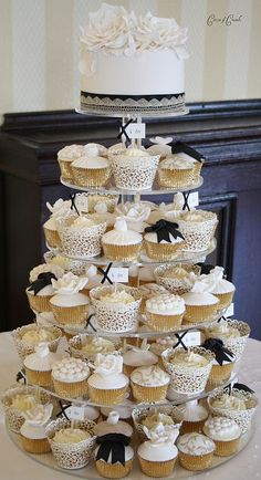 Vintage themed gold and black cupcake tower display with a layer of wedding cake on top #wedding #gold #goldblack #cupcaketower #weddingcake