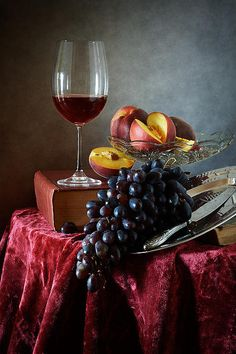 http://nikolay-panov.artistwebsites.com/products/peaches-and-grapes-nikolay-panov-art-print.html • Still life with glass of red wine, grapes, fresh peaches and old vantage books.