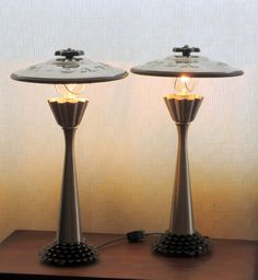 These graceful twin silver-and-black lamps are made from a pair of brushed metal candlesticks, dessert molds, bicycle gears, and vintage Volvo hub covers, plus assorted bits of this and that.