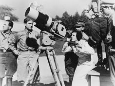 """Filmmaker Leni Riefenstahl looks through the lens of a large camera prior to filming the 1934 Nuremberg Rally in Germany. The footage would be composed into the 1935 film """"Triumph of the Will"""", later hailed as one of the best propaganda films in history. (LOC)"""