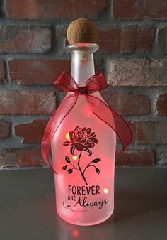 Bottle light is made from a frosted liquor bottle decorated with red glitter, green, and black vinyl with a red bow around the … Wine Bottle Candles, Wine Bottle Corks, Painted Wine Bottles, Lighted Wine Bottles, Bottle Lights, Bottle Lamps, Liquor Bottles, Glass Bottles, Glass Bottle Crafts