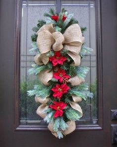 A rustic country Christmas swag in burlap with pine, lightly snowed spruce stems, pine cones  pretty mini poinsettias for a burst of color.: