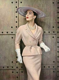 Lucky in lightweight glazed wool suit, the jacket has rounded shoulders and shawl collar, tied at the waist with cord of same material by Pierre Balmain, photo by Pottier, 1954