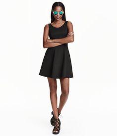 En ärmlös klänning i trikå. Klänningen är avskuren i midjan, djupt ringad i ryggen samt har cirkelskuren kjol.