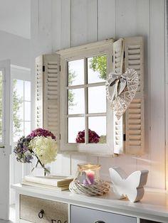 un miroir style romantique, dans une ancienne fenêtre avec des volets en persienne