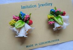 "Genuine 1950s earrings. Made in Czechoslavakia by Imitation Jewellery Very cute flower bouquets, 3 trumpets (coloured either red, yellow or blue) surrounded by smaller flowers in pink, red, blue, and yellow and green foilage. They sit on the ear when worn- 1950s style! Quite delicate. The fastening is a standard metal clip. Pretty! These earrings have recently been rediscovered as part of an amount of deadstock. It has never been worn and is genuinely vintage! They measure approx. 1"" X 1..."
