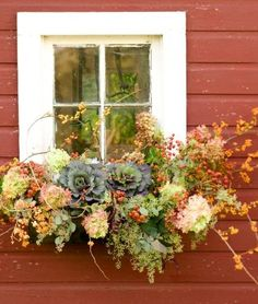 Fresh and dried flowers make for a bountiful fall look. Oversize cabbages and hydrangea blossoms anchor an arrangement that has branches twisting out in fun swirls. See more ideas for decorating with hydrangeas: http://www.midwestliving.com/homes/seasonal-decorating/fall-decorating-with-hydrangeas/?page=3