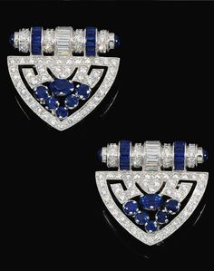 A pair of sapphire and diamond dress clips. Each designed as an open work plaque set with circular-cut and baguette diamonds, embellished with mixed-cut sapphires.