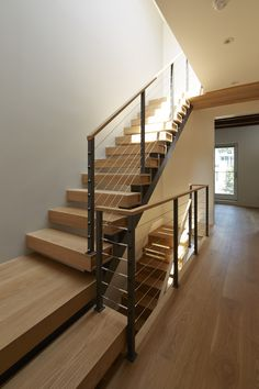 White oak plain sawn stairs with cable railing and wood cap.