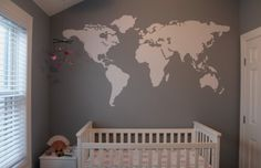 A travel themed nursery in grays, white, and pink with large map of the world decal.